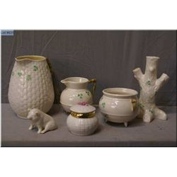 A selection of Irish Belleek including tree trunk vase, pitcher, cream and sugar, pig figure and  hi