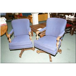 A pair of upholstered swivel office chair on castors