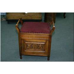 An antique commode with padded seat, double  handles and carved door