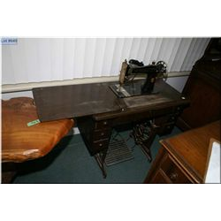 An antique Singer treadle sewing machine in a  quarter cut oak cabinet
