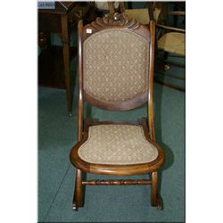 A vintage upholstered folding nursing rocker