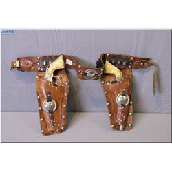 "A pair child's of ""Wild Bill Hickok"" six shooters in leather holster-note one gun missing appliqué"