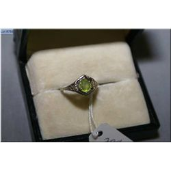 An antique deco style ladies stamped 14kt white  gold ring set with peridot green stone