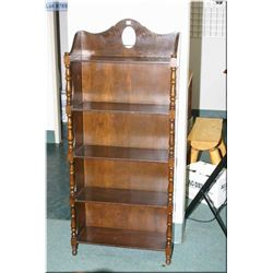 A five tier walnut open bookcase with decorative turned supports