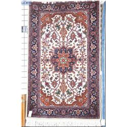 """A small wool area rug with center medallion, cream back and multicoloured patterned background 60"""" X"""