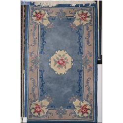 A small sculpted floral area rug with center medallion and decorative corners in multiple blue tones
