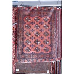An Iranian wool area rug with geometric pattern and multiple borders in muted tones of salmon and  r