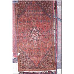An Iranian wool area rug with center medallion and overall geometric pattern, in colours of red, sag