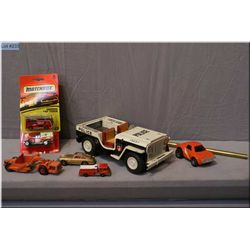 A selection of vintage toys including Japanese made tin Police jeep, matchbox cars and tractors etc.