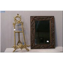 A wooden and hand carved framed mirror and a brass picture easel