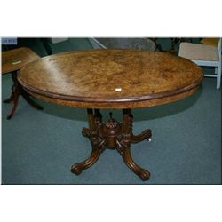 A Victorian burl walnut splayed leg occasional table with inlaid foliage and original porcelain cast