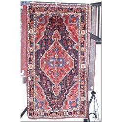 An Iranian wool area rug with large center medallion and geometric border in multiple red and blue t