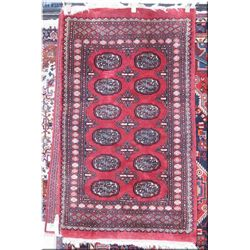 "A small wool area rug with wide multiple borders and geometric center on  a red background 38"" X  64"