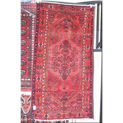 An Iranian wool area rug with center medallion, geometric floral pattern in multiple red tones 44""