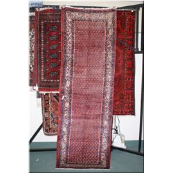 An Iranian wool area rug with fine geometric pattern and multiple wide border is soft red and  blue