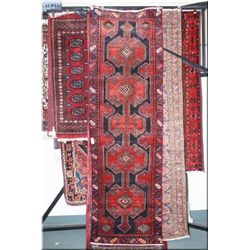 An Iranian wool runner with multiple medallions, geometric border in deep reds and blue colours 36""