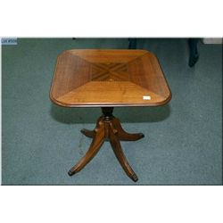 A vintage matched grain mahogany single pedestal table with brass capped feet and inlaid top