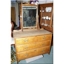 A four drawer mirrored oak dresser