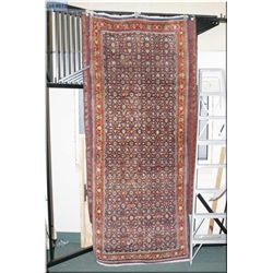A Iranian made wool area rug with overall  geometric floral design in shades of navy, reds  and mute