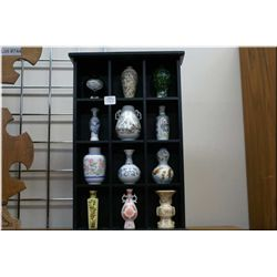 A selection of Oriental style miniature vases in a wall mount display