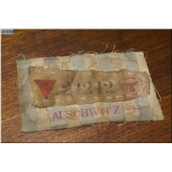 Auschwitz Jewish Prisoner's Badge on a scrap of Concentration Camp uniform featuring the yellow Jewi