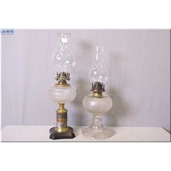 Two antique oil lamps, both colourless glass with hurricanes, one on metal pedestal