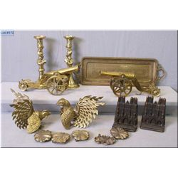 A selection of collectible brass including serpent motif candle sticks, cast book ends, two cannons