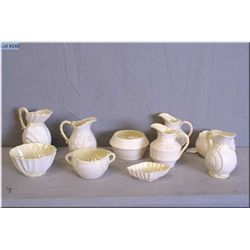A collection of Belleek cream and sugars including Cleary and Nautilus patterns, plus a small nut di