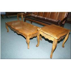 An oak coffee table and two end tables with carved skirt and legs
