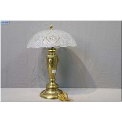 A cast brass lamp with lion head decoration and a etched glass shade