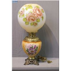 A vintage oil style electric lamp with handpainted floral detail and glass globe