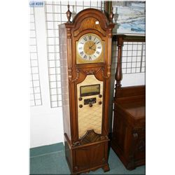 A vintage long case clock motif, walnut cased clock and radio made by Howard