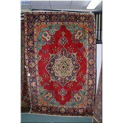 An Iranian Trabriz 100 % wool area rug with floral motif, large medallion in shades of teal, red and