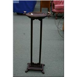 An antique floor standing ashtray with attached cigar cutter