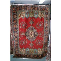 An Iranian Tabriz area rug with large center medallion, and matching shield motif edge in shades of