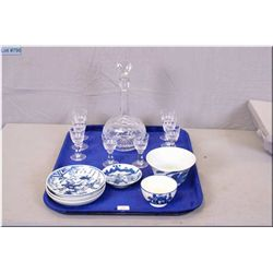 A crystal decanter with eight matching liqueur glasses and a selection of blue and white Asian porce