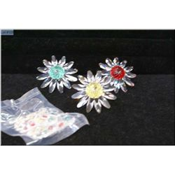Three Swarovski crystal flower ornaments and a small bag of floral ornaments