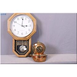 An electric Regulator style wall clock and a miniature copper diver's helmet