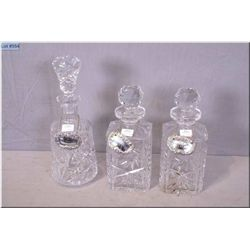 Three pinwheel crystal decanters with stoppers and silverplate drinks labels