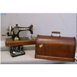 Antique Singer portable sewing machine in a wooden carrying case