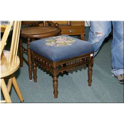 An antique Canadiana stool with floral needlepoint upholstery