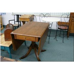 A mid 20th century center pedestal drop leaf dining table with brass capped and storage drawer