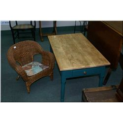 A child's sized wicker chair and a painted side table with a drawer