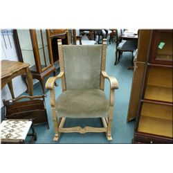 Heavy framed European oak rocking chair with upholstered seat and back and nail head and tastefully