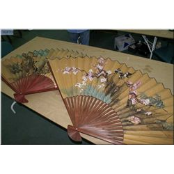 Two large wall mount Oriental fans
