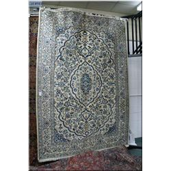 Naen wool area rug with center medallion, all over floral pattern in shades of creams, blue and brow