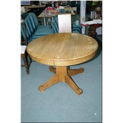 """A 42"""" center pedestal oak dining table with three insert leaves"""