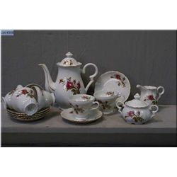 A rose motif tea set including six cups and saucers, tea pot, lidded sugar and cream- note repair to