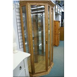 A modern oak four tier illuminated corner display cabinet with bevelled glass doors