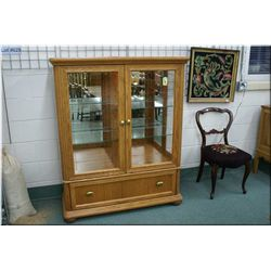 A modern illuminated two door display cabinet with glass shelves, note hinge activated lights